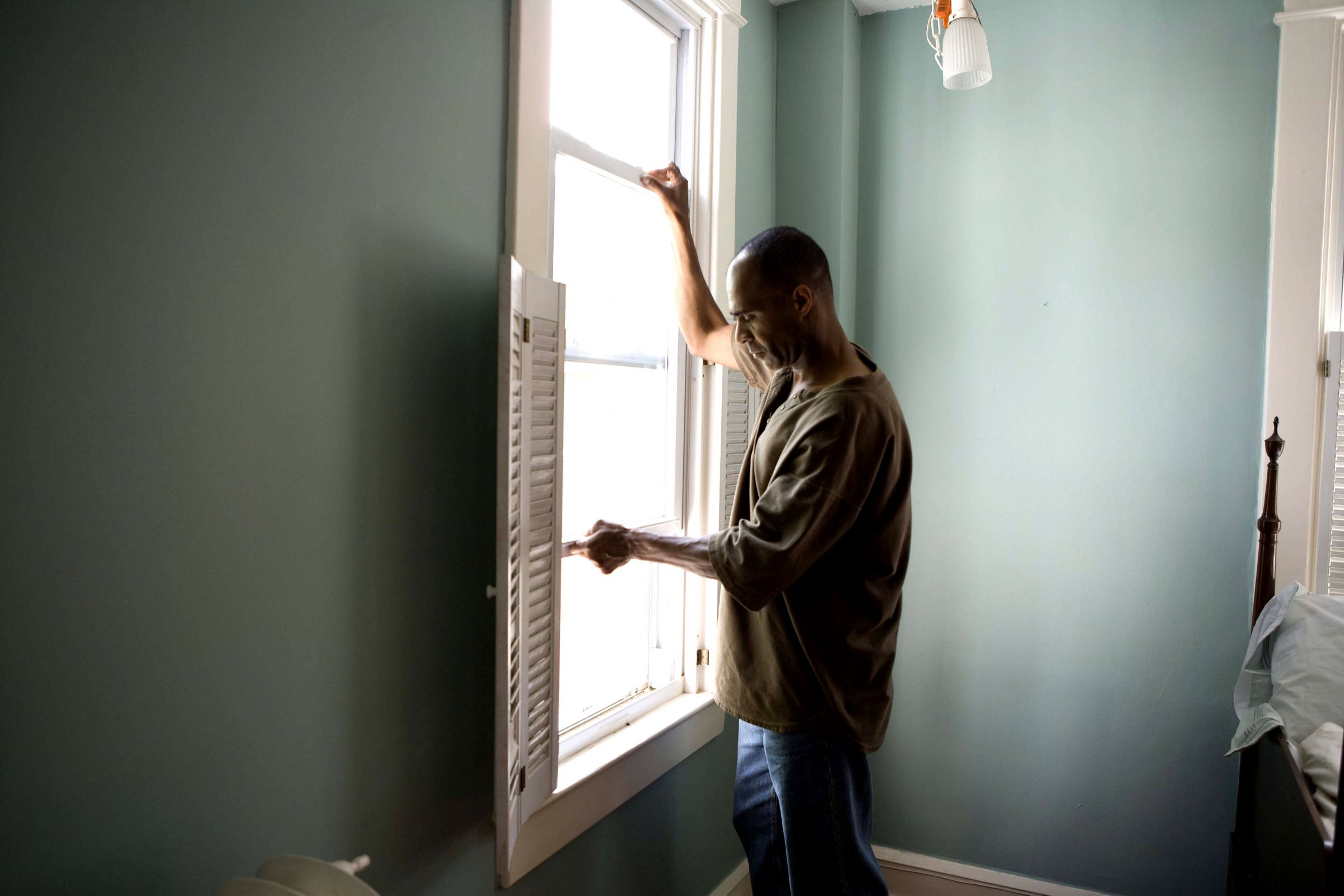African American man opening window at his home